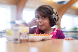 Young girl eats lunch at school cafeteria table