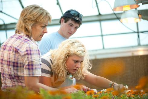 Mary Hausbeck examines flowers inside a greenhouse with her students.
