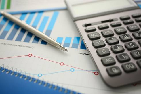 Financial report with calculator and pen