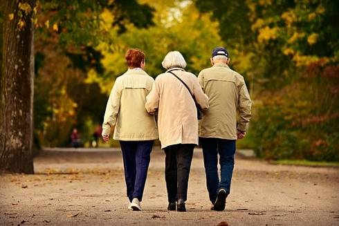 three elderly people walking together during a nice fall day