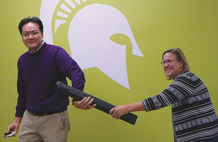 Photo of Karen Russcher passing the baton to Jun-Hyun Kim.