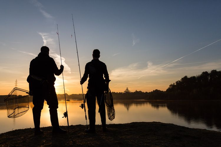 Two fisherman stand on the shore of a freshwater lake at sunrise
