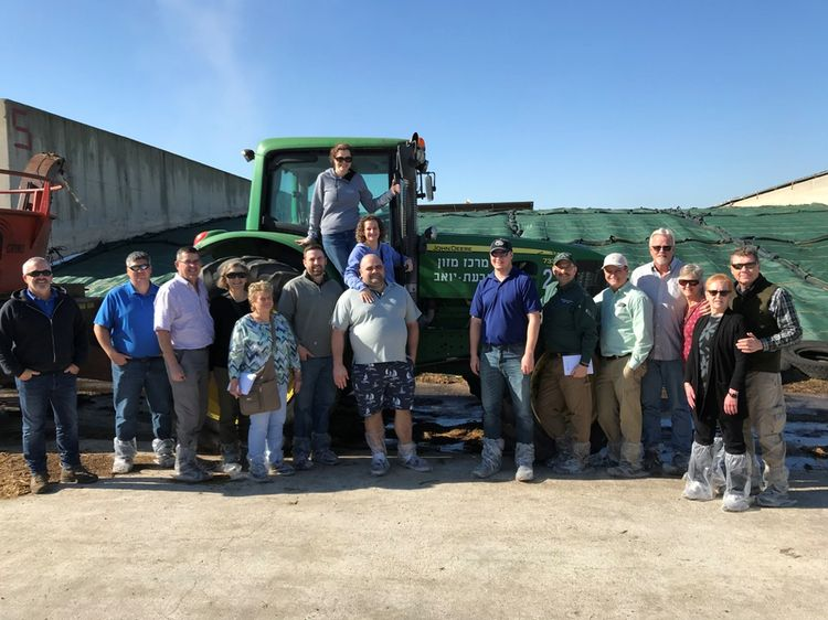 A group of people standing in front of a tractor