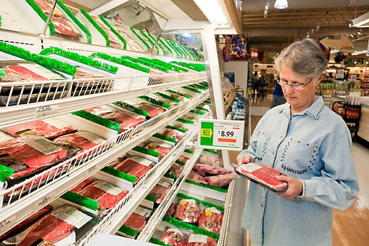 A woman looking at meat in a grocery store.