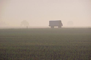 A picture of a large vehicle driving on a foggy morning across a field.