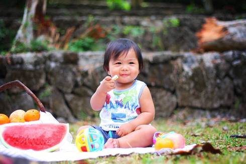 Toddler in front of fruits at a picnic.