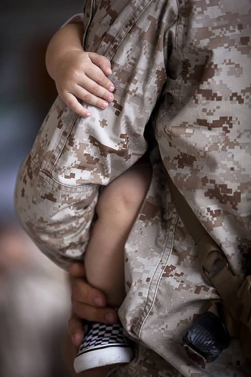 Military dad holding kid
