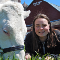 MSU agribusiness management student Lynn Olthof with cow on a farm.