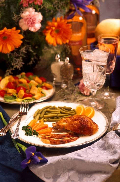 Thanksgiving meal with a plate piled with turkey, green beans, carrots and oranges.