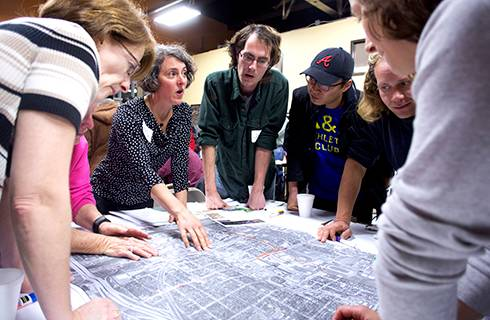 Photo of group working together on plan documents during a charrette.
