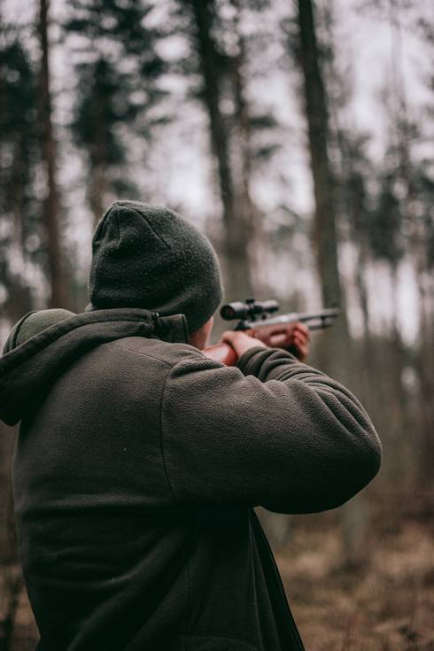 Man holding rifle in woods.