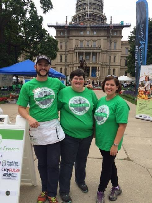 MSU Extension staff members working at MIFMA's August 27, 2015 Farmers Market at the Capitol. Pictured from left to right: Extension Educators Garrett Ziegler, Julie Darnton, and Kendra Wills.
