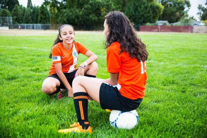 Girls sitting on soccer field with ball