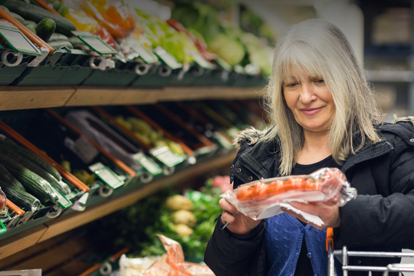 Woman with white hair looks at fresh tomatoes in a grocery store.