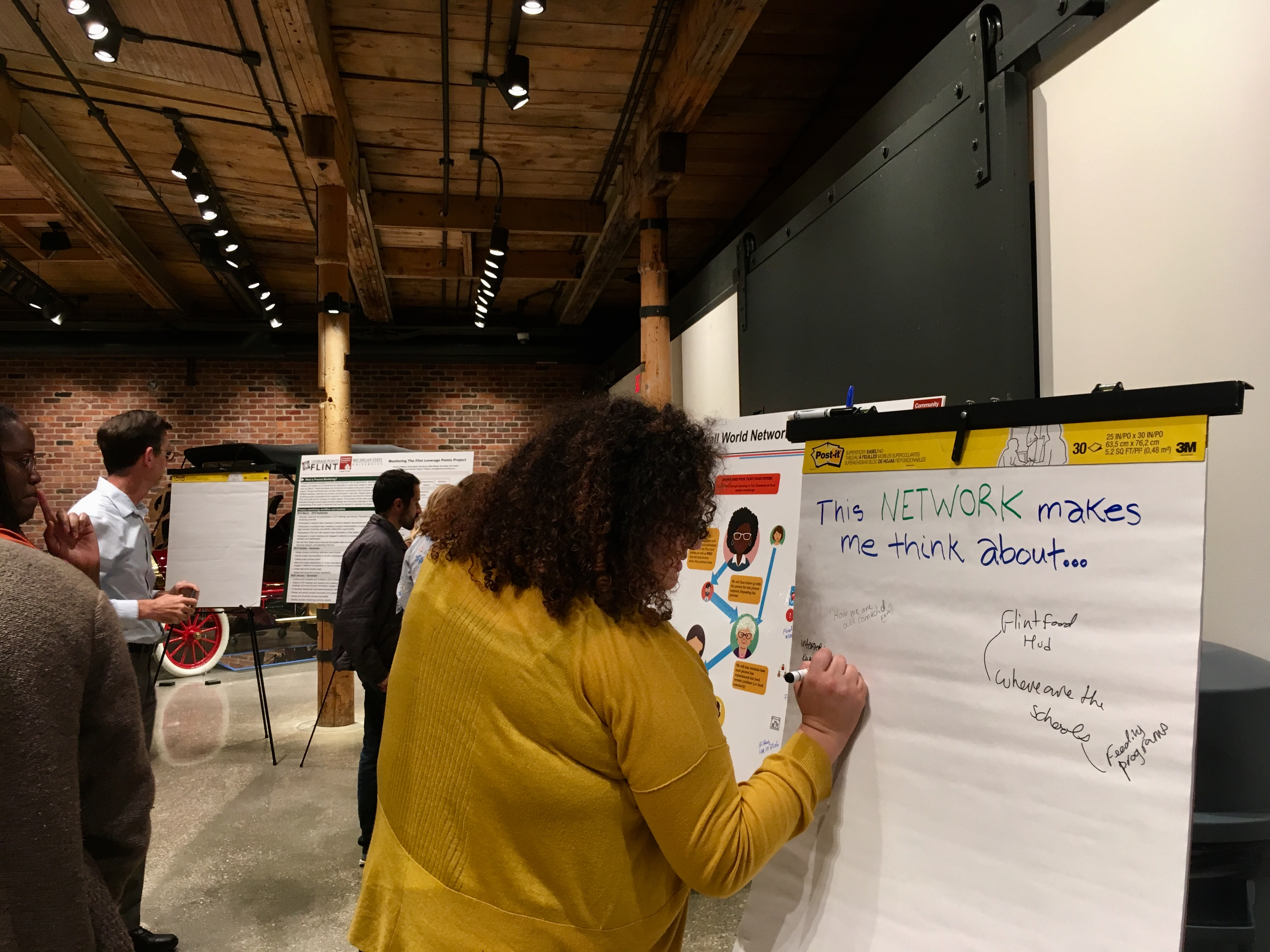 Woman writes on a flip chart at a community forum in Flint