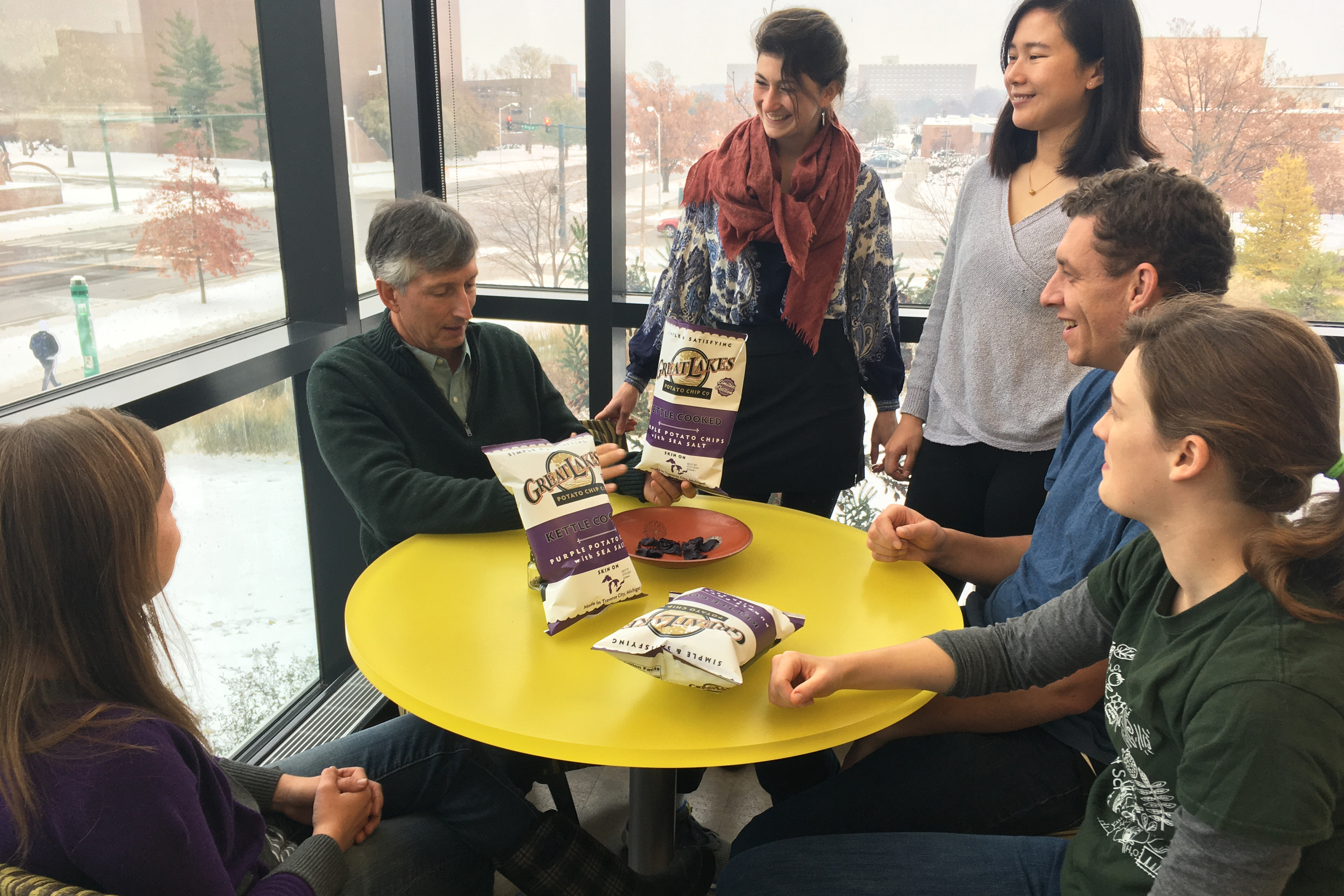 MSU potato breeder Dave Douches eats purple potato chips with students