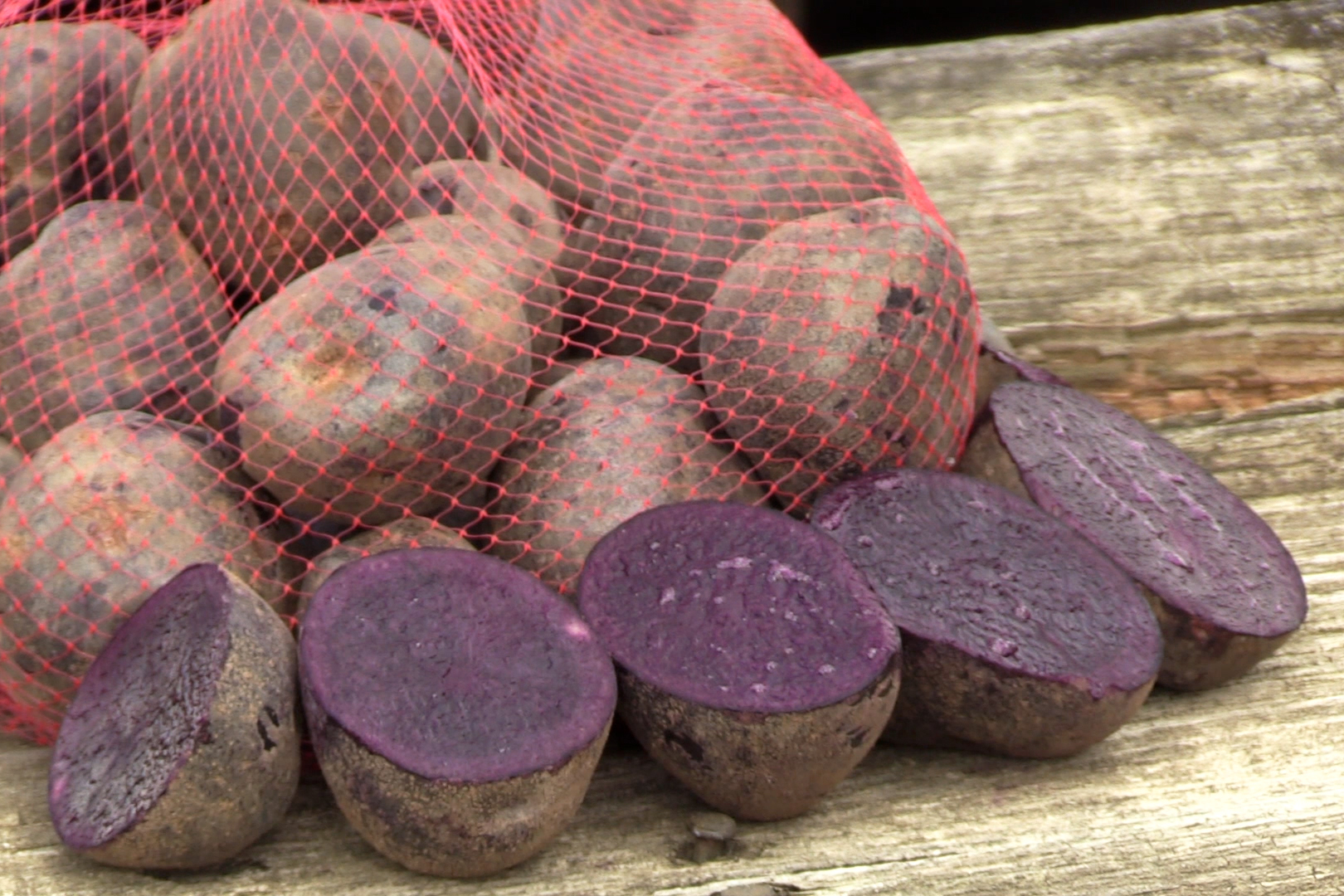 purple potatoes cut in half and in bag