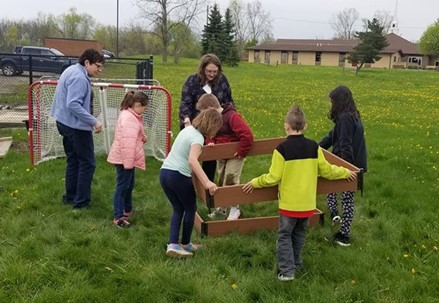 Adults and youth carry a raised garden bed