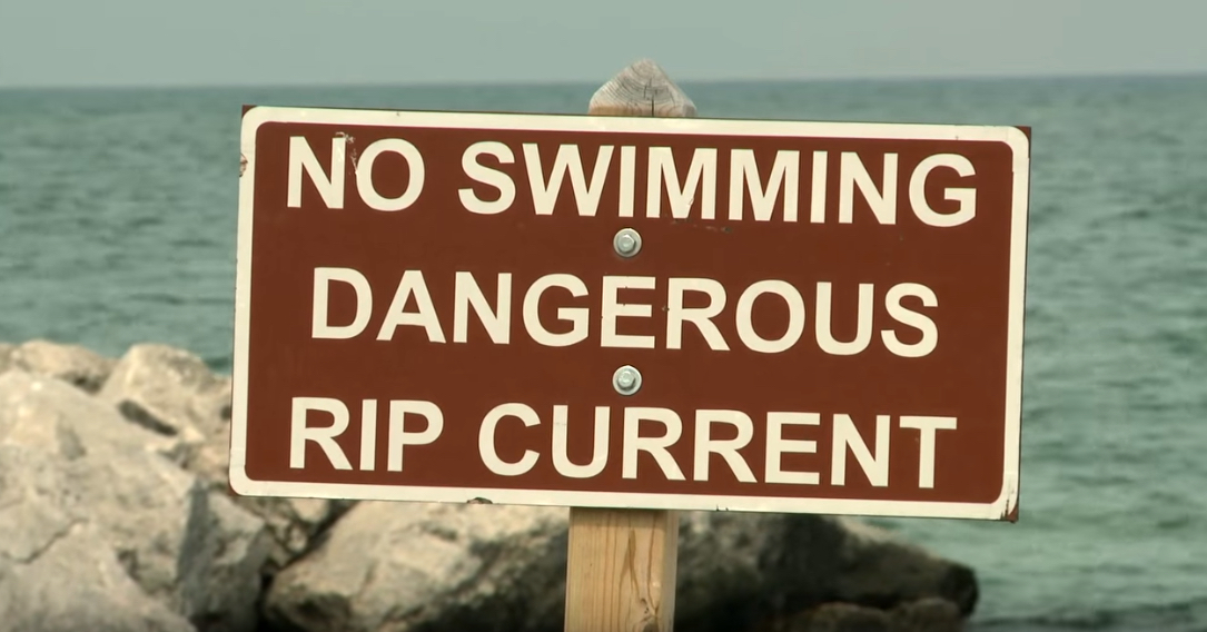 A sign by the water states: No swimming. Dangerous Rip Current.