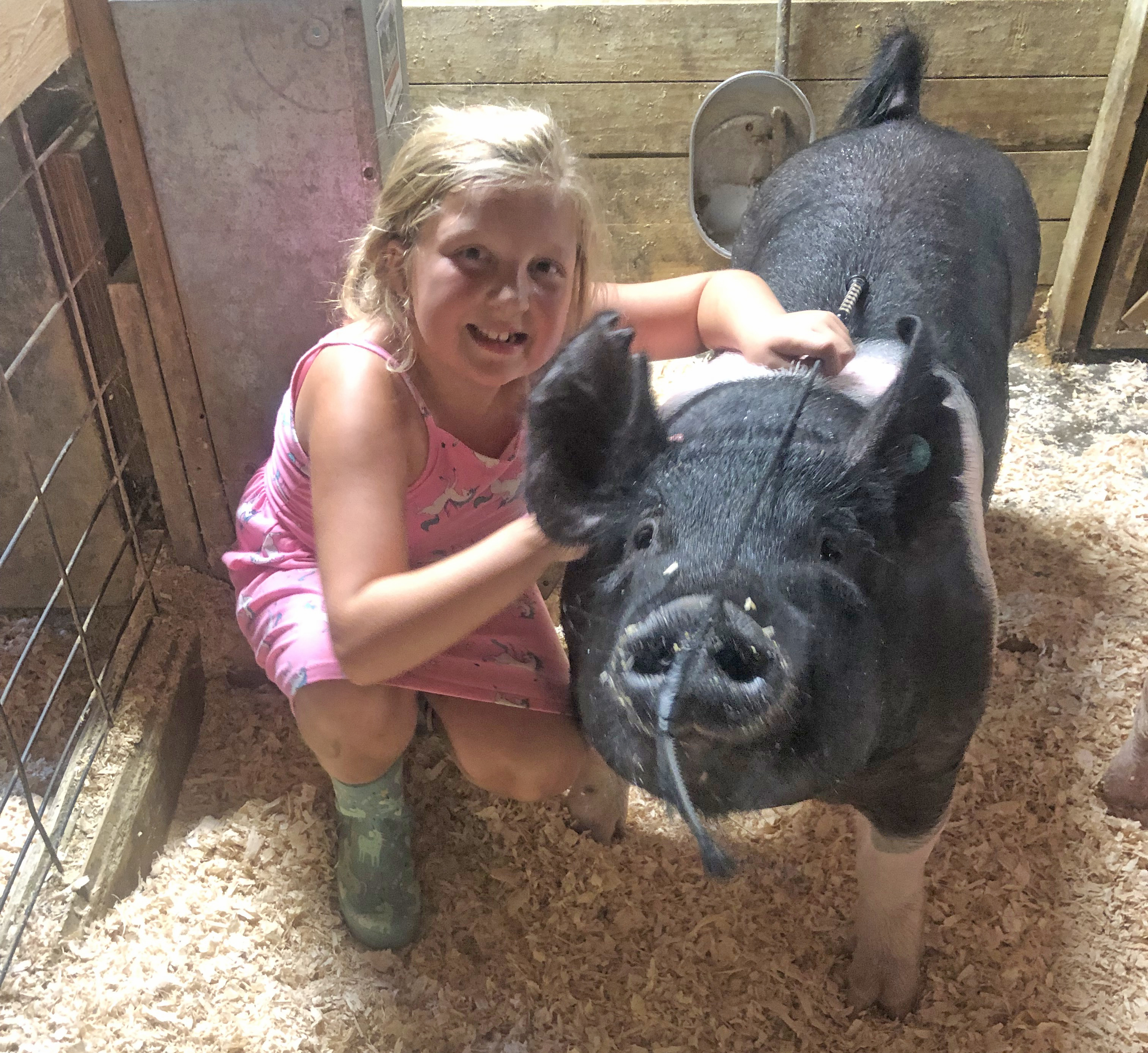 A girl posing for a picture with her pig.