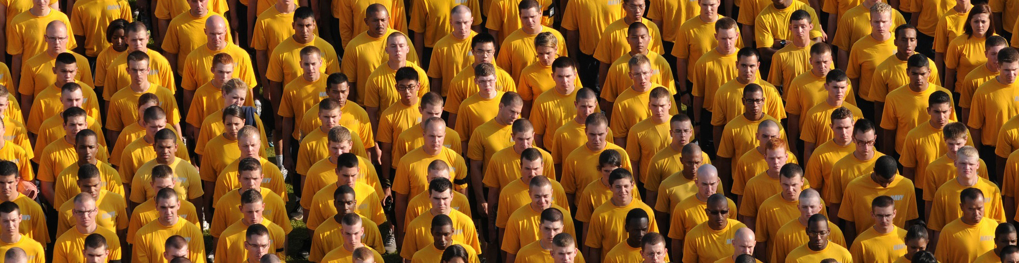 Group of men and women wearing yellow shirts standing shoulder to sholder in tight rows.