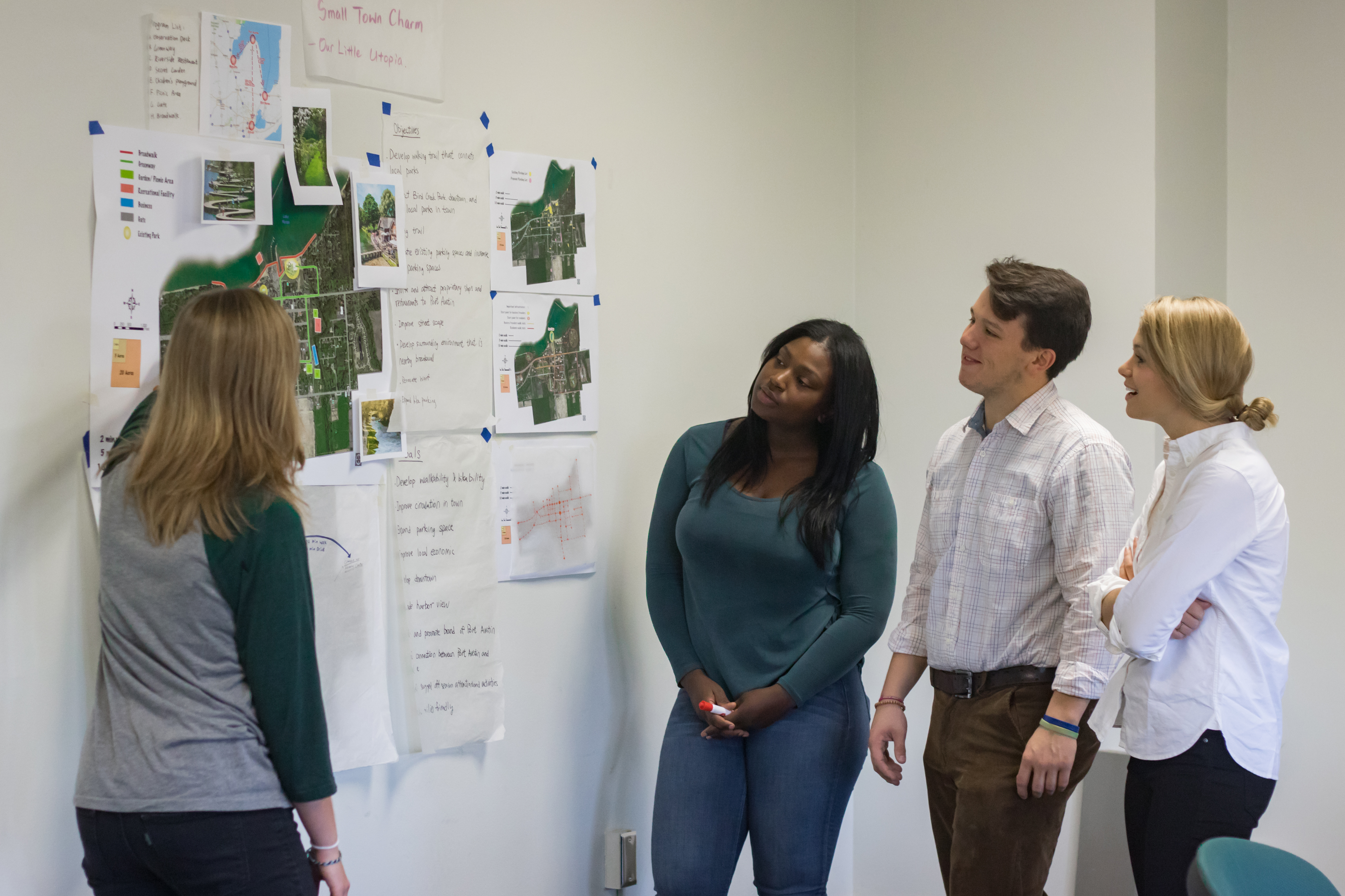 Urban and Regional Planning student presenting a poster while others watch.
