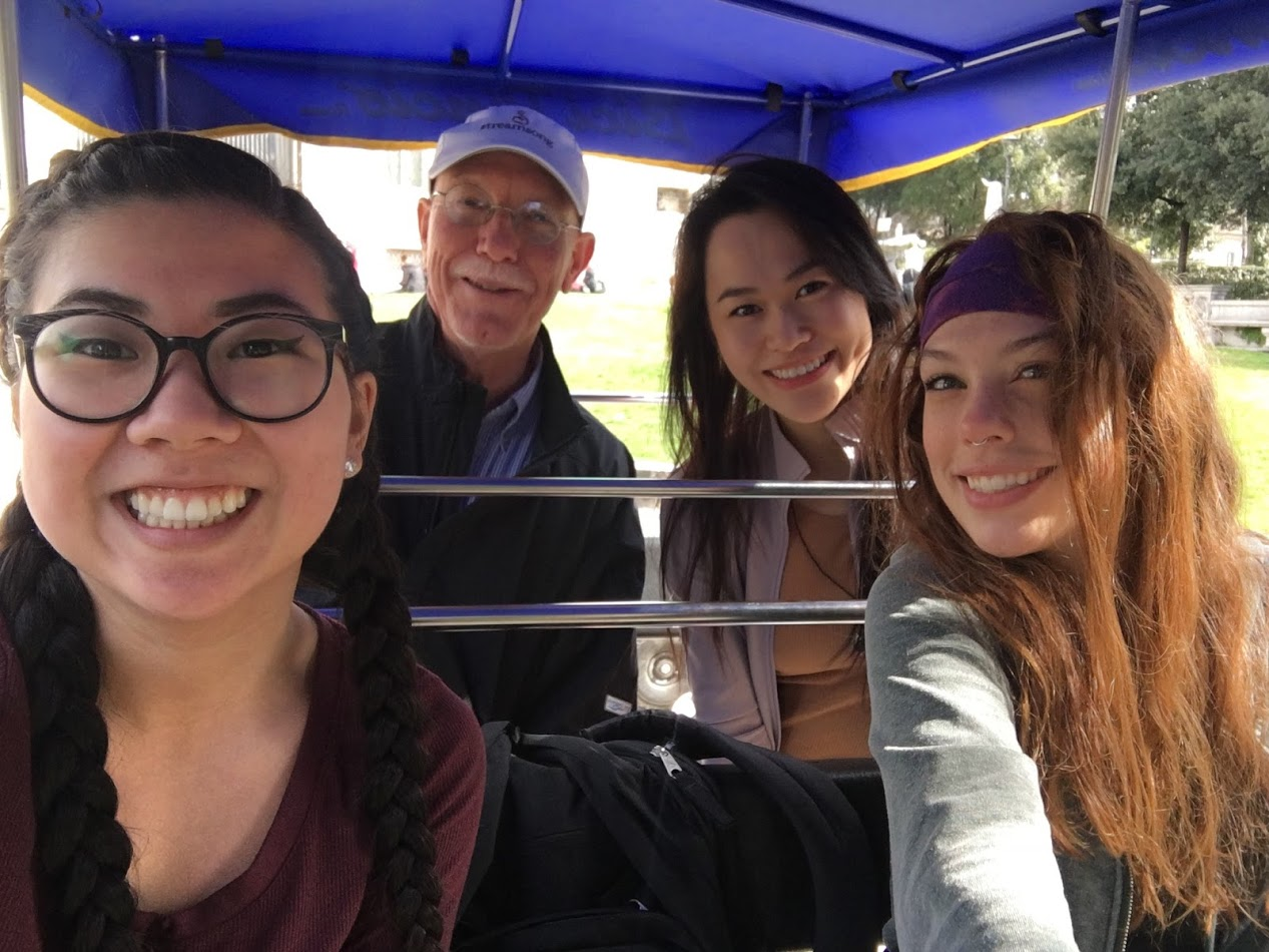 Students and faculty sitting in a pedal carriage.