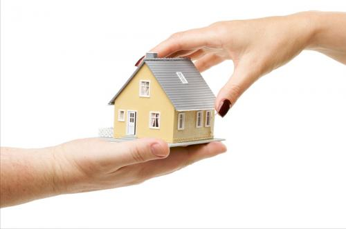'image of house being transferred from one persons hand to another persons hand'