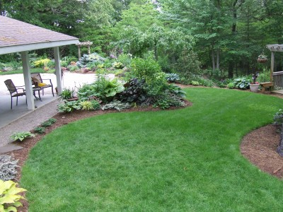 A backyard with a patio, flowers, and a well-manicured lawn.