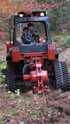 Tractor and vibratory plow operating in a forest stand.