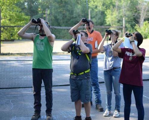 Youth look through binoculars at birds.