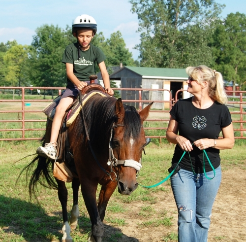 Extension Specialist walks with young boy on horse as part of therapy