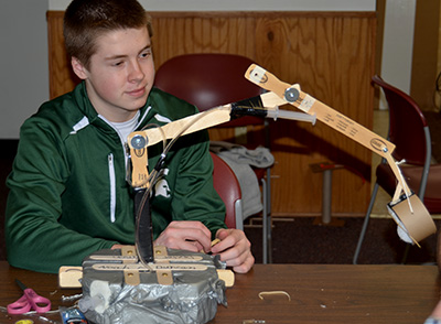 Youth making a robotic arm