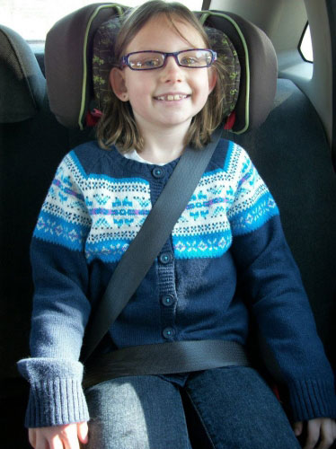An eight-year-old child sitting properly in a booster-seat.