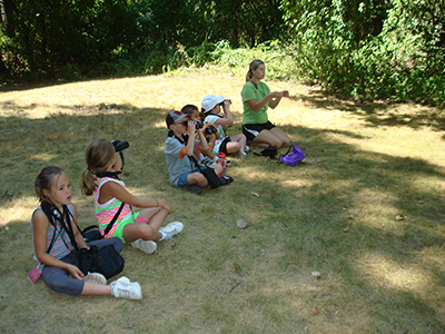 Youth birdwatchers sitting on grass