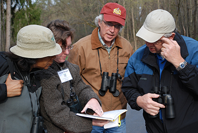 Birdwatchers look at a bird ID guide