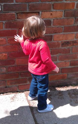 CHILD AT BRICK WALL