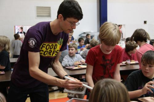 FoodCorps volunteer serves food to kids