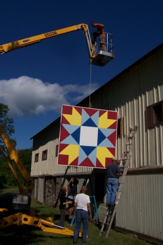 Hoisting quilt onto barn