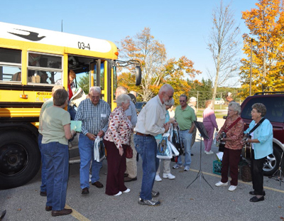 Participants in the annual Alcona County George Byelich Memorial Fall Color Tour get off the bus to visit their next site.