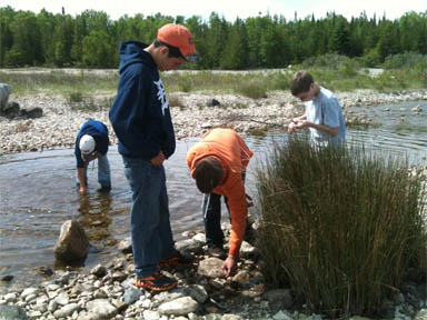 Students exploring the shore in Thompson's Harbor State Park in Michigan.