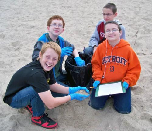 Four boys doing Adopt-A-Beach clean up image.