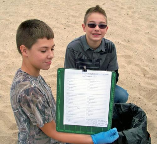 Two boys tracking Adopt-A-Beach clean up image.