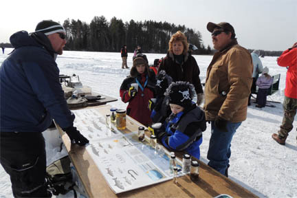 Family learning about ice fishing image.