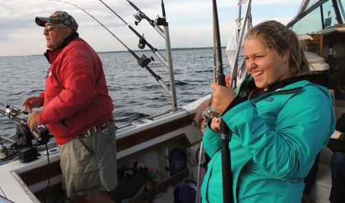 4-H girl fishing on charter boat with captain
