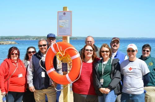 Staff and volunteers pose in front fo a safety ring and post. Photo credit: Michigan Sea Grant
