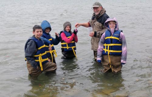 Adult volunteer with students collecting water samples image.
