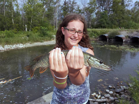 Girl holding fish at Great Lakes Natural Resources Camp 2013 image.