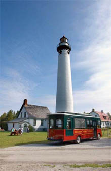 Tour bus in front of lighthouse image.